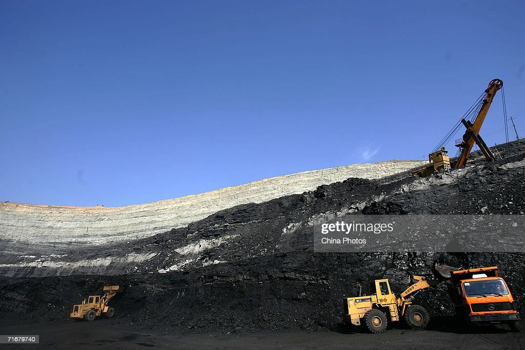 A frontend bucket loader moves coals into a coal hauling truck in an open pit coal mine on August 19 2006 in Chifeng of Inner Mongolia Autonomous...