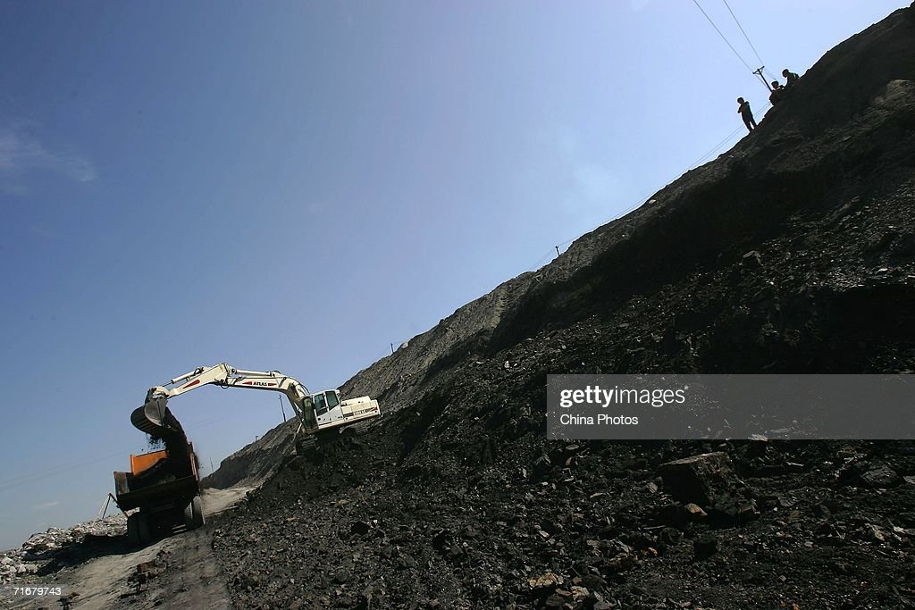 A front-end bucket loader moves coals into a coal hauling truck in an open pit coal mine on August 19, 2006 in Chifeng of Inner Mongolia Autonomous Region, China. Pingzhuang Coal Groups Company, including six open pit coal mines, produces 10 million tons per year. Reportedly, in the first four months of this year, China's coal consumption rose by 13.8 percent over the same period of last year, and coal price is expected to go up steadily with the factors of environment, safety and resources included in the cost of coal production.