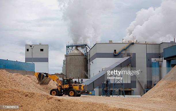 A frontend loader moves wood chips into the West Fraser Timber Co pulpmill in Quesnel British Columbia Canada on Thursday July 11 2013 West Fraser...
