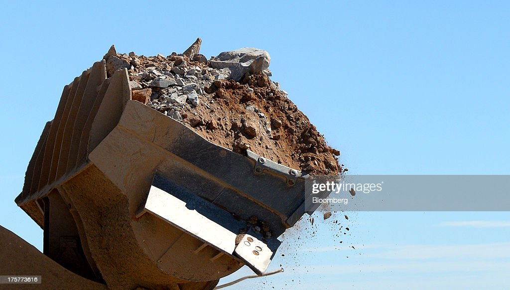 A front-end loader tips ore into a crushing machine at the Norton Gold Fields Ltd. Paddington operations 35 kilometers north-west of Kalgoorlie, Australia, on Wednesday, Aug. 7, 2013. Norton, the Australian producer controlled by China's Zijin Mining Group Co., is seeking further acquisition targets as falling prices cut the value of mines. Photographer: Carla Gottgens/Bloomberg via Getty Images