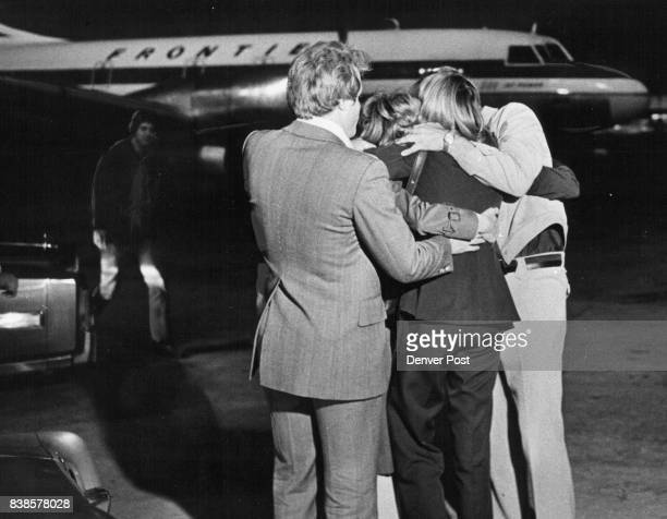 Frontier Airlines stewardess Diane Lord back to camera U hugged by friends at Stapleton International Airport after being flown home from Atlanta Ga...
