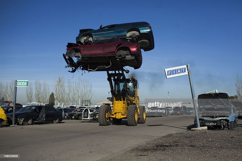A front-loader moves scrapped automobiles past a Fiat SpA and a Skoda Auto AS sign in the yard of the Desguaces La Torre scrapyard in Madrid, Spain, on Thursday, Dec. 13, 2012. Spain has completed the debt sales it planned for this year and started raising funds for 2013, buying time for Prime Minister Mariano Rajoy as he decides whether to seek a European bailout. Photographer: Angel Navarrete/Bloomberg via Getty Images