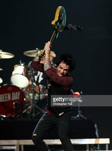 Frontman Billie Joe Armstrong of Green Day smashes his guitar as he performs onstage during the 2012 iHeartRadio Music Festival at the MGM Grand...
