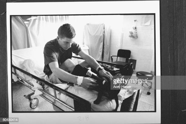 Frostbite victim Jim Stolpa adjusting therapy boots as he lies in bed at Washoe Medical Ctr Jim wife Jennifer baby son Clayton were stranded in a...