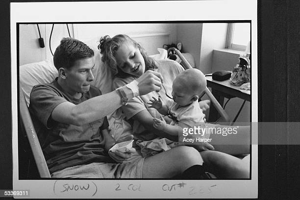 Frostbite victim Jim Stolpa spoon feeding baby son Clayton while wife Jennifer looks on in bed at Washoe Medical Ctr they were stranded in a blizzard...