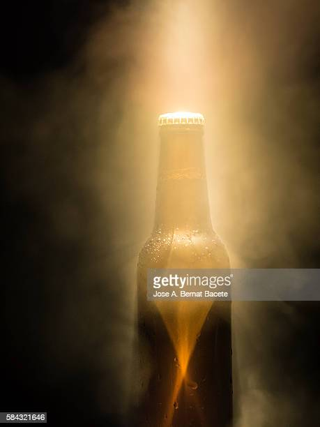 Frosty and cold bottle of beer on a black background in an environment of smoke