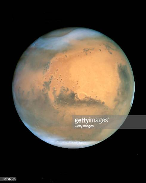 Frosty white ice clouds and swirling orange dust storms float above a vivid rusty landscape on Mars June 26 2001 in this sharpest view ever obtained...