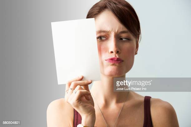 Frowning Caucasian woman holding blank card
