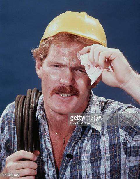 Frowning Construction Worker Cleaning Sweat