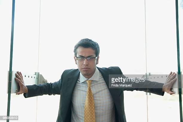 Frowning Hispanic businessman opening doors