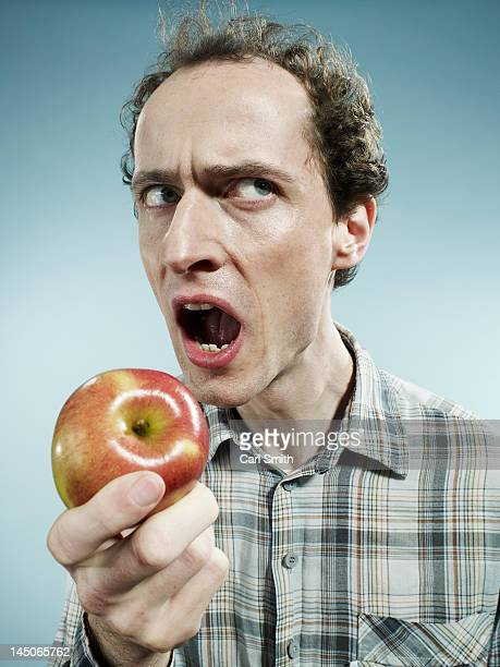 A frowning man preparing to bite into an apple