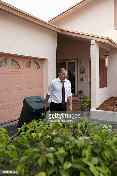 A frowning man pulling a trash can down his driveway