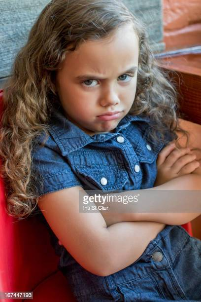 Frowning mixed race girl sitting in chair