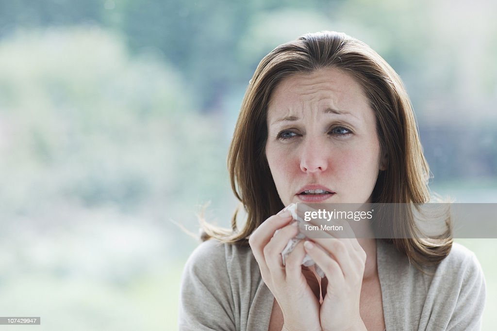 Frowning, sick woman holding tissue