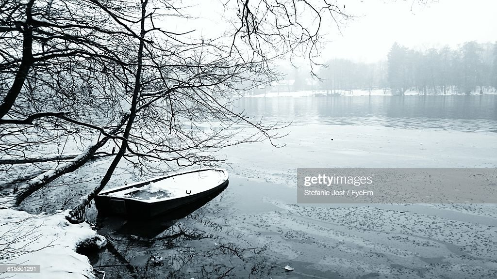 Frozen Boat Moored In River By Tree During Winter