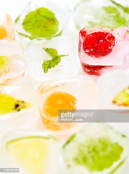 Frozen herbs and fruits in ice cubes, close-up