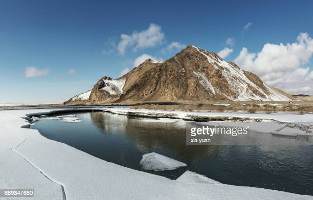 Frozen lake surrounded by snow on Bayanbulak,China