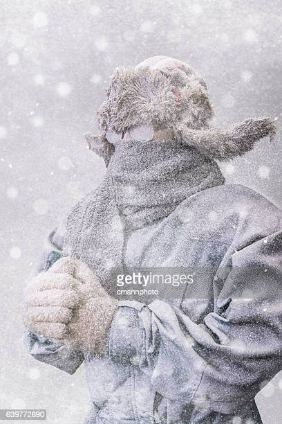 Frozen man in parka, hat and scarf as snow falls