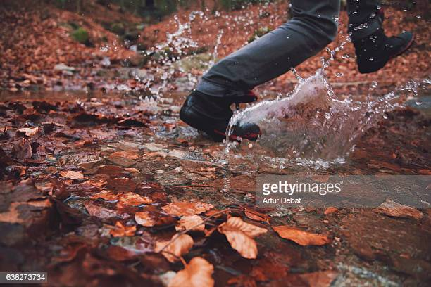 Frozen moment of a guy doing trekking in the Montseny nature reserve, stepping the river with nice splash during the autumn season.