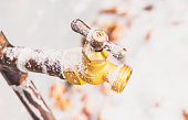 Frozen outdoor water faucet covered in snowflakes