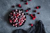 Frozen raspberry, blueberry, cranberry on dark background. Frozen fruit. Top view, flat lay