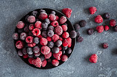 Frozen raspberry, blueberry, cranberry on grunge background. Frozen fruit. Top view, close up