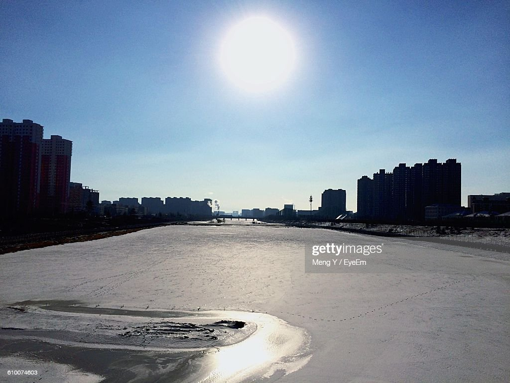 Frozen River Canal In City Against Sky