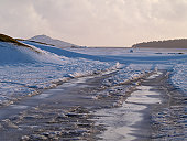 Frozen road and snow covered countryside