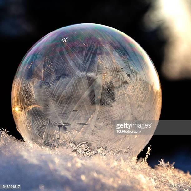 A frozen snowflake in a soap bubble