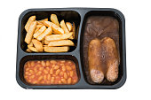 Frozen TV dinner of sausages in gravy with chips and baked beans.