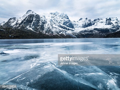 Frozen water and mountain range on background