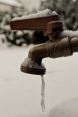 A small amount of water freezes into an icicle as it comes out of a tap, snow covers the ground in this picture. The tap has a snow covered red handle. This picture could be used to symbolize the prob