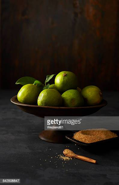 Fruit bowl with limes and bowl of cane sugar