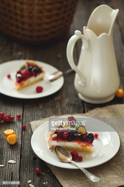 Fruit cake with fresh berries and milk on a wooden table.