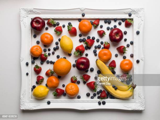 Fruit colourfully displayed in a white picture frame on a white background