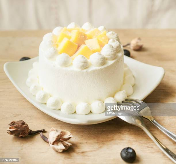A fruit cream cake on a white plate is placed on the table