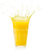 yellow juice spilling out of a glass isolated on white