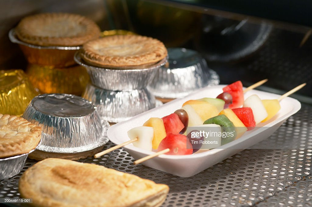 Fruit kebabs and meat pies in display case : Stock Photo
