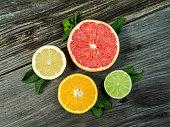 Photo of a sliced grapefruit, orange, lemon, and lime on a old rustic slab of barn board.