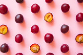 Fruit pattern of beautiful, fresh, whole and half of plums on pastel pink background. Healthy sweet food concept. Flat lay. From top view.