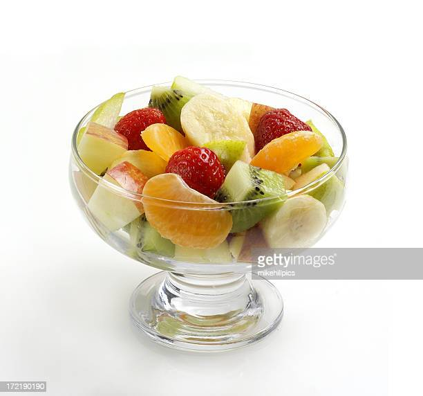 Fruit salad in footed glass bowl on white