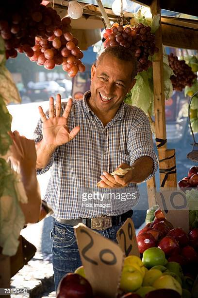 Fruit seller holding money and gesturing, Santo Domingo, Dominican Republic