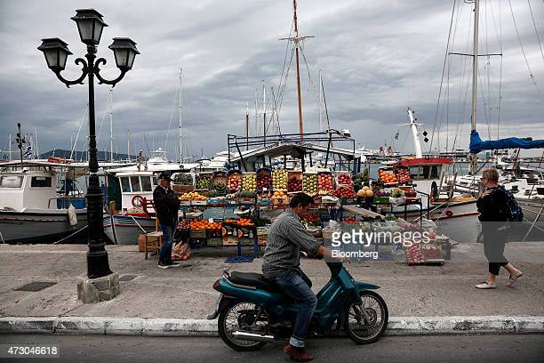 A fruit seller waits for customers beside his stall at the harbor side on the island of Aegina Greece on Monday May 11 2015 Less than three weeks...