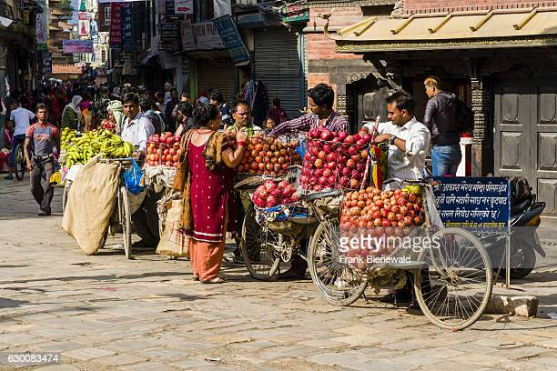 Fruit sellers using bicycles are offering apples and oranges on Indra Chowk in front of Akash Bhairab temple