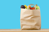 A brown paper shopping bag, filled to the top with varieties of fruit, on a light wood surface.  Isolated on a turquoise blue background.