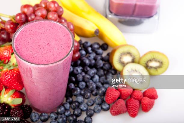 A fruit smoothie with fruit around it