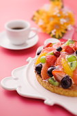 Fruit tart and a cup of coffee, red background