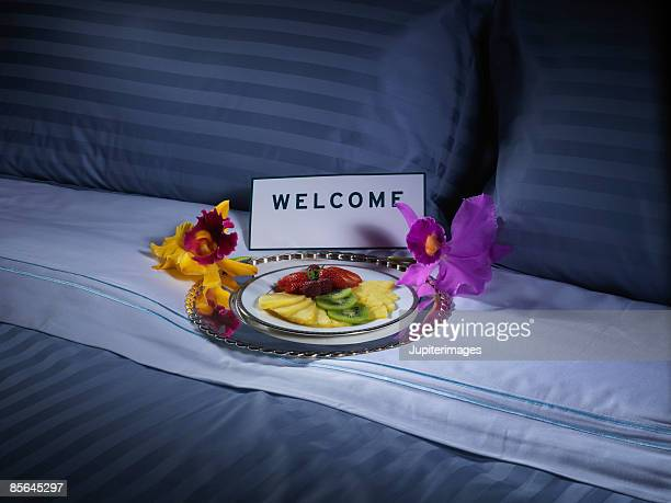 Fruit tray and welcome sign on hotel room bed