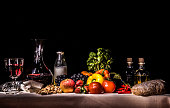 A light painting photograph showing fruit, vegetables, milk, wine, oil, vinegar, bread on a set table against a dark dramatic background giving it the look and feel of a renaissance flemish painting