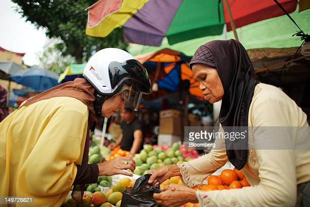 A fruit vendor assists a customer at a market stall in Jakarta Indonesia on Thursday Aug 2 2012 Indonesia is expected to release secondquarter gross...